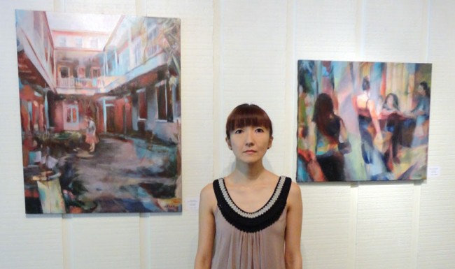 Isoko Onodera in front of her oil paintings on display at Frameworks Gallery in Baton Rouge