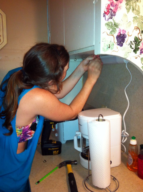 Kristen Schroeder installs hooks beneath the kitchen counter at the House of Destiny.