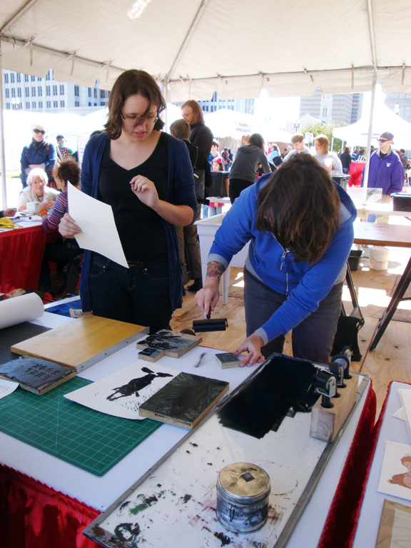 LSU printmaking graduate students demonstrating relief printing at Louisiana Book Festival