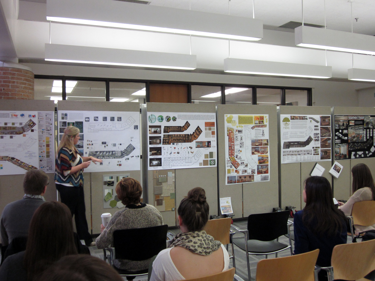 An Interior Design Student Presents Her Final Project To Faculty Jurors And Peers During