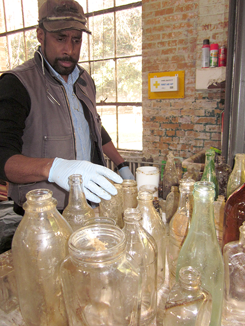lsu school of art visiting artist nari ward inspects glass bottles