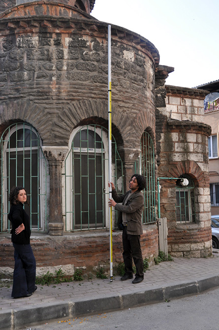 People surveying stone mosque exterior