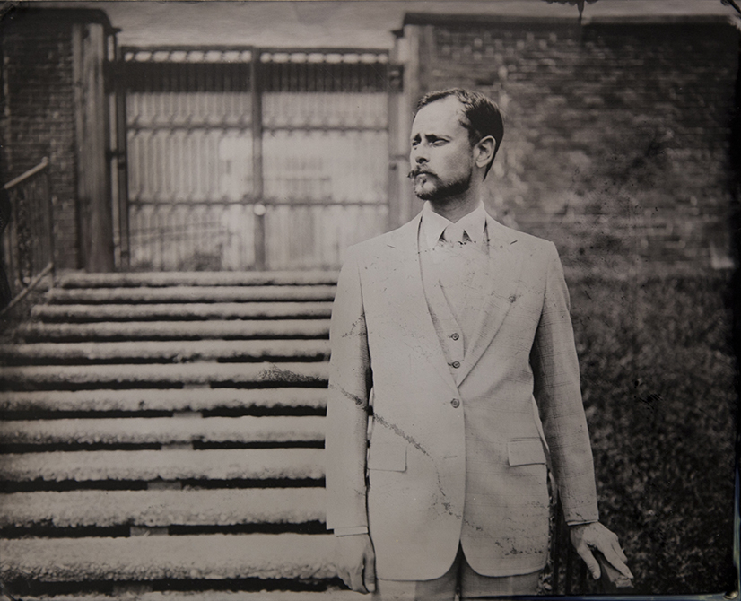 Man in suit with mustache, old fashioned grainy black ad white photo quality. lsu photography graduate student Ian Minich