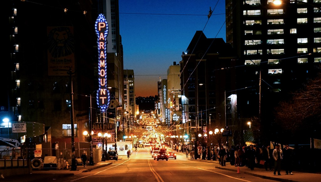 """City scene at night with glowing sign """"Paramount"""""""