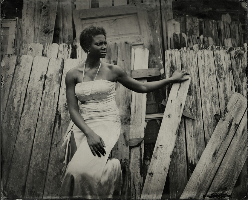 Black and white portrait of black woman by broken fence. lsu photography graduate student Ian Minich