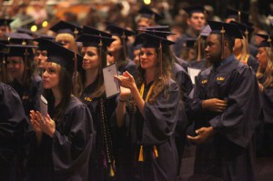 Students in purple robes applaud at graduation