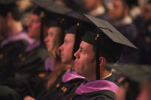 Line of people seated in black robes and caps at graduation ceremony