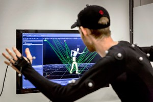 Man looks at screen with simulated figures, raised hand attached to wires