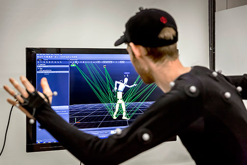 Man looks at screen with simulated figures