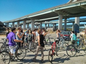 Students with bikes by overpass in Oakland