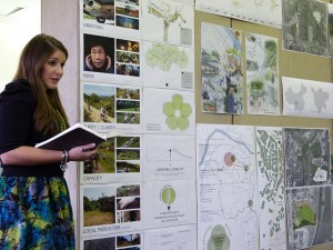 Female student presents work, poster on wall