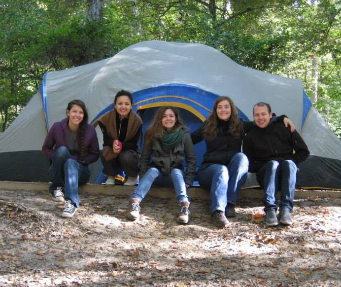 Smiling students in front of tent, trees in background