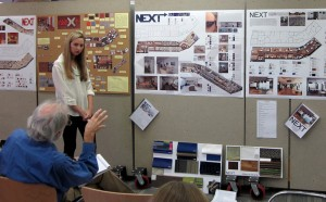 Student stands by project on wall as professor critiques work at lsu interior design final reviews
