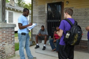 Young African American man chats with family on house front porch