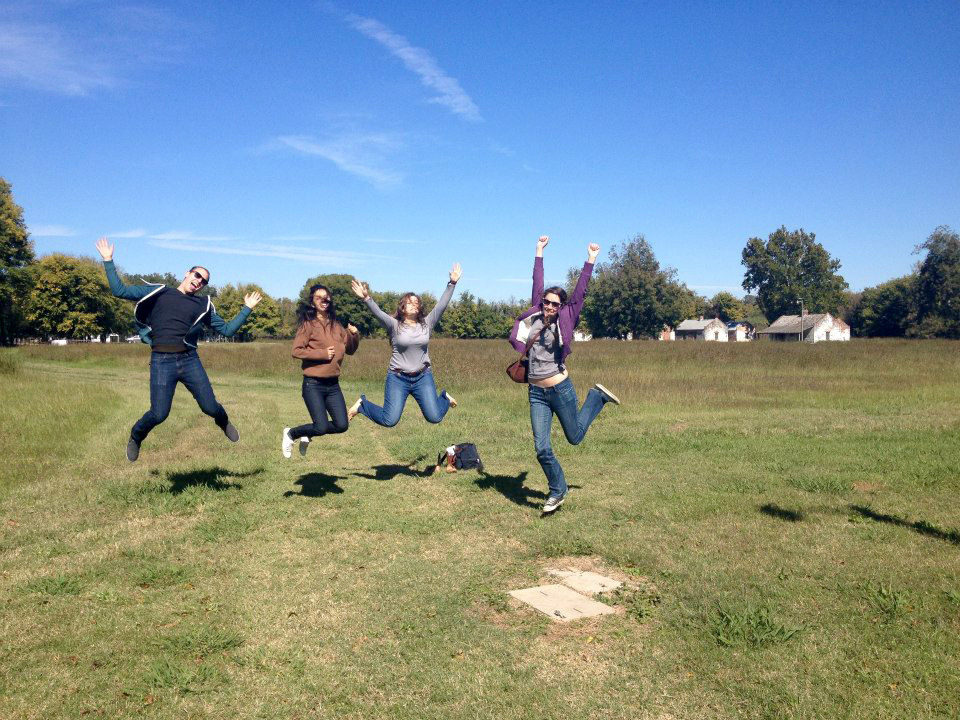 Female students jumping in grassy field, bright blue sky