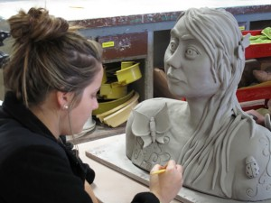 Female ceramics student creates clay bust of woman