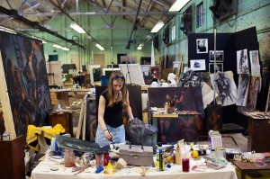 Young woman works at table covered in art supplies, in large warehouse setting