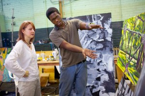 Tall male African American student gestures to painting while professor studies work