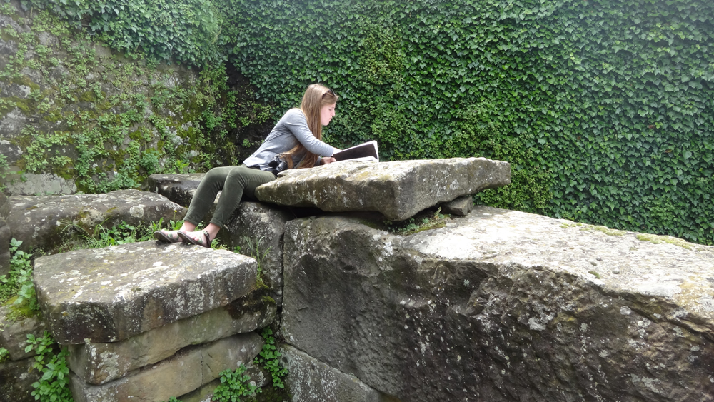 Student sketching on stone wall in garden