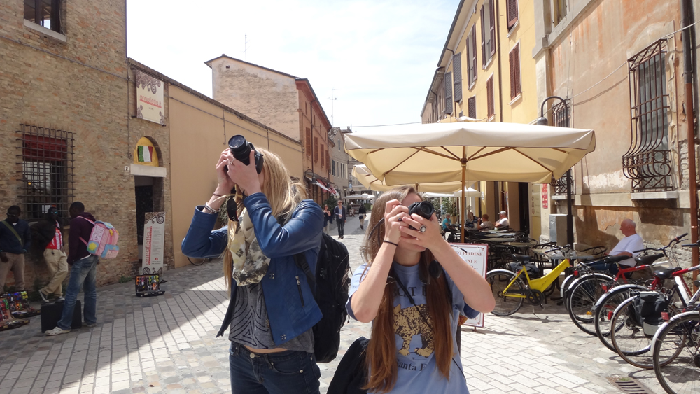 Female students hold cameras in Florence piazza