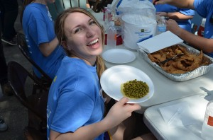 Smiling student holding plate of food at LSU interior design service learning project