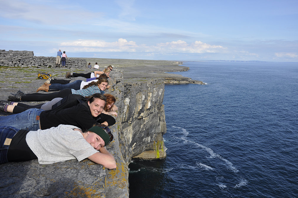 Students lie on steep cliffs over the ocean