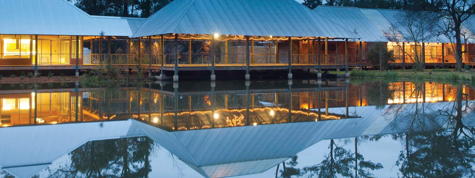 LSU Hilltop Arboretum at twilight, illuminated building reflected on pond water