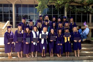 Group of interior design students in purple robes hold diplomas on steps after graduation ceremony