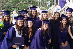 Smiling students in purple caps and gowns