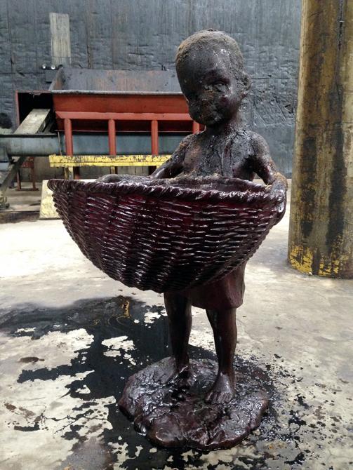 Sculpture of child holding basket