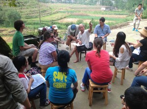 Group in rural Chinese setting, rice patty fields in background