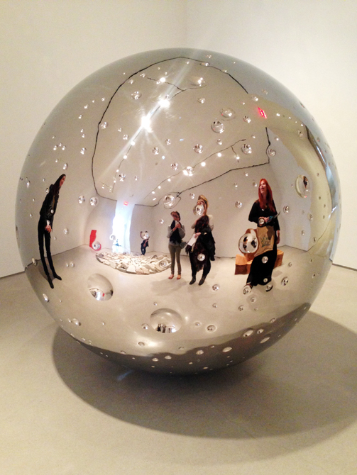 Reflection of students in a silver orb