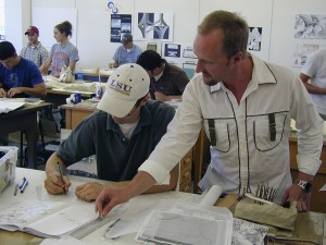 lsu landscape architecture faculty works with student in white LSU baseball cap