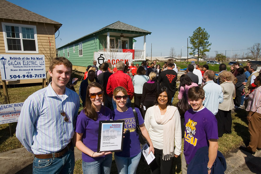 ASLA students help rebuild the Ninth Ward in New Orleans, wearing purple shits; houses in background