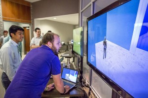 Male students look at images on large screen at lsu future fest