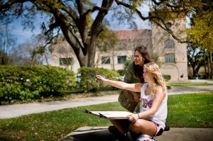 Student points, while holding sketchpad, as instructor looks on in campus plaza