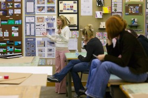 Female students present in interior design studio with walls covered in design projects