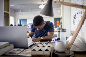 Male student works at laptop in lsu architecture studios