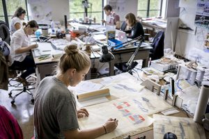 Blonde female student works at table in lsu architecture studios, other students in background