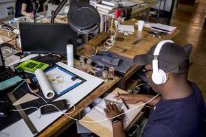 Young African American man works with white headphones on in lsu architecture studios
