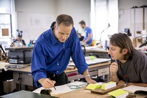 Architecture professor Tom Sofranko in blue shirt leans over students desk