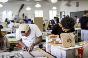 Students grin as they lean over their work in the lsu architecture studios