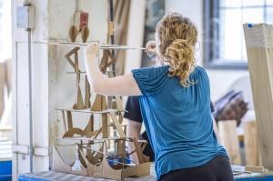 Young woman in blue shirt assembles sculpture