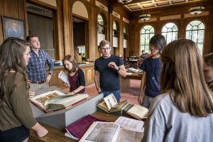 Students and professor around manuscripts in library
