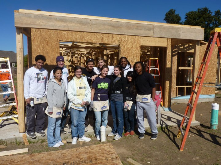Minority students smile in front of Habitat for Humanity construction site