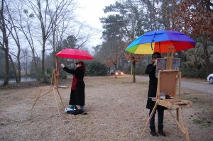 Figures under brightly colored umbrellas, at easels outside surrounded by trees