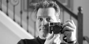 Robb Williamson black and white portrait, holding camera