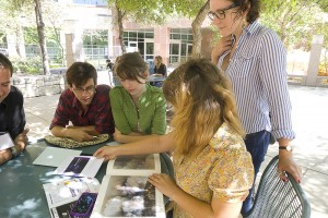 SNAP students visit Society for Photographic Education Conference, gather around table