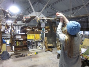 Female student in blue cap working on sculpture in large warehouse studio