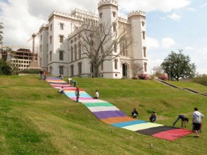 Students assemble colorful path on lawn in front of Old Louisiana State Capitol building